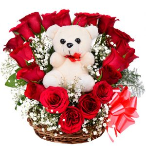 18 Red Roses in heart shape and 1 Cute Teddy Bear in a Basket.
