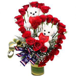 24 Red Roses, 2 Teddy Partners and 6 Cadbury Chocolates along with Green leaves decoration