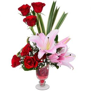 8 Roses with 5 Pink Lily in a transparent Flower holding Vase.
